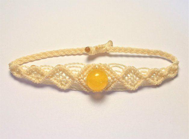 Es handelt sich um ein geknüpftes Makrameearmband aus gewachsten Garn in der Farbe Hellgelb mit einer gelben Perle.