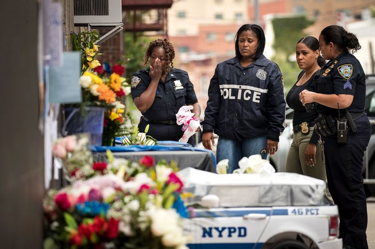 """Colleagues visit a makeshift memorial for fallen NYPD officer Miosotis Familia outside the 46th Police Precinct on July 6. Familia, 48, was shot and killed as she sat in a command vehicle in the Bronx, in what police called an """"unprovoked attack."""""""