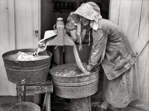 "Through the Wringer -May 1938. Irwinville Farms, Georgia. ""Mrs. Coleman doing a washing."" Slow but steady progress in the science of mechanized laundry"