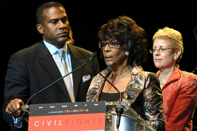 The Hon. Maxine Waters speaks as Tavis Smiley and Nancy Zirkin look on. The Denver event honored civil rights organizations.