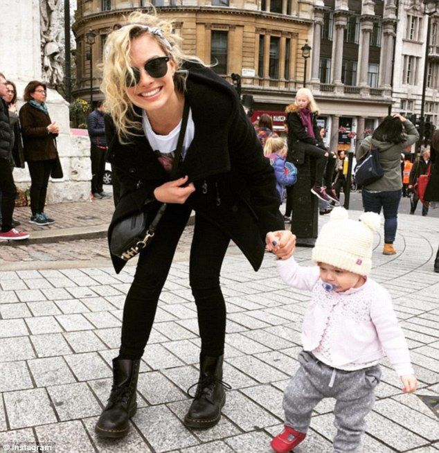 Happiness:Margot Robbie showed off a large smile on Monday as she walked hand-in-hand with her beau Tom Ackerley's young niece while they watched the tiny tot's father compete in the London Marathon