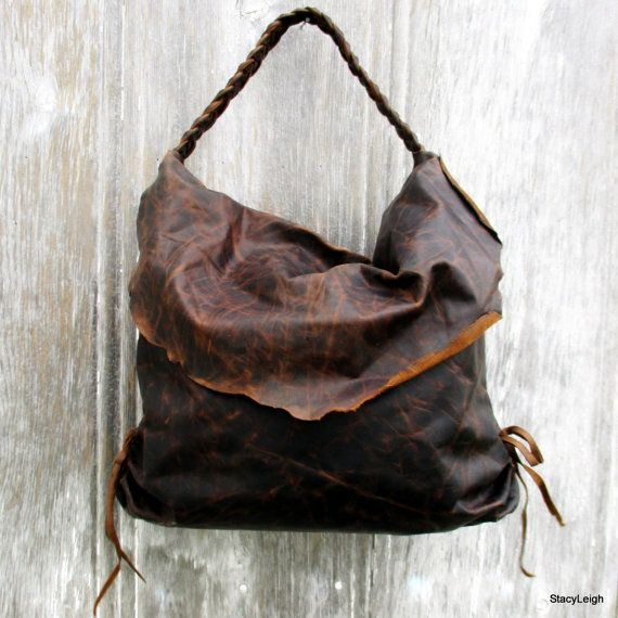 Very distressed, dark brown leather with great character. The bag is 18 by 13 by 4.5 with a short braided strap that creates a hobo look. Rustic, leather flap flips over the top of the bag. Magnetic snap at top inside. Lined in velvet with 2 distressed leather, drop in pockets. Ruched sides with long leather ties can be tied in bows or knotted and trimmed to desired length. The leather will soften and continue to distress with use.