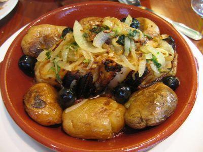 """Bacalhau à Lagareiro: bacalhau assado servido com azeite de alho junto com batatas assadas, conhecidos como """"Batatas AO Murro""""."""