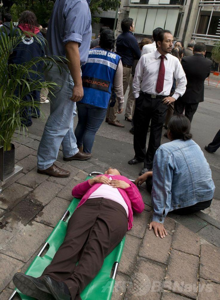メキシコの首都メキシコ市(Mexico City)で、地震の発生後に地面に横たわる女性(2014年5月8日撮影)。(c)AFP/Yuri CORTEZ ▼9May2014AFP|メキシコ南部でM6.4の地震、道路橋が倒壊 http://www.afpbb.com/articles/-/3014459