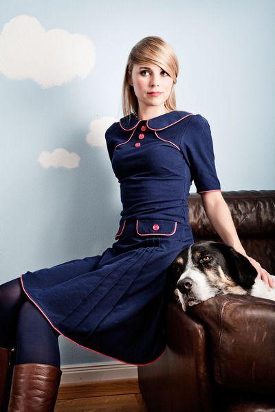 Das Kleid wird aus einem marineblauen Jerseystoff angefertigt und wurde mit vielen roten Knöpfen und Paspelband verziert. Am vorderen und hinteren ...