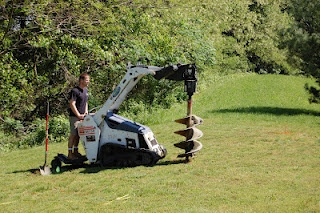 Digging holes to install a residential ground mount solar array