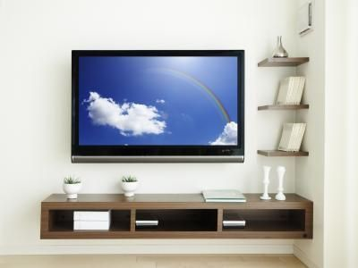 Use floating shelves to decorate your wall-mounted television.