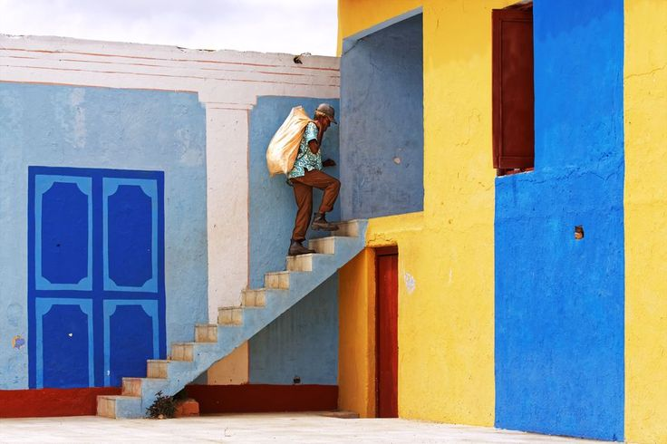 A worker in Trinidad, Cuba climbs up the stairs in a colorful building located in the city center.