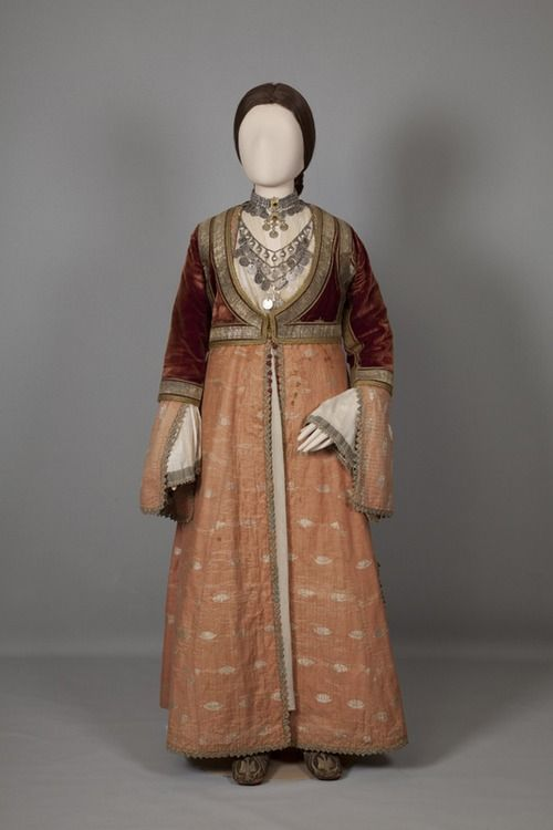 Urban women's costume of Pyrgos, Ilia, Peloponnese. Mid/late 19th c. © Peloponnesian Folklore Foundation, Nafplion, Greece  The urban costume of Pyrgos is unique and was taken as the model for the 'Amalia' costume. It consists of a white silk-and-cotton chemise with gold braid on the sleeves, a kavádi (dress) of pink and white brocade and an old-style zipoúni (jacket) of crimson velvet adorned with braid, gold-brocaded ribbons and a little gold embroidery round the edges and on the…