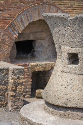 Ancient Bakery in Pompeii, Italy. Detail of grindstone and oven in the background: