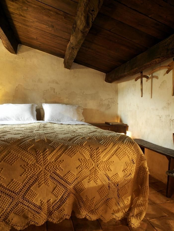 Bed in medieval hotel in Italy with yellow crochet bedspread..plaster walls.