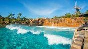 Waves break in Disney's Typhoon Lagoon Surf Pool with Mount Mayday beyond