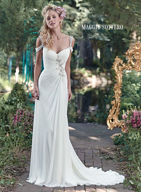 Saxton wedding dress by Maggie Sottero   This elegant Gossamer chiffon sheath gown is sweetened with a ruched bodice, accented with a Swarovski crystal and pearl embellishment. Finished with crystal cold-shoulder sleeve, plunging V-back and crystal buttons over zipper closure. Detachable Gossamer chiffon Watteau train offered separately.