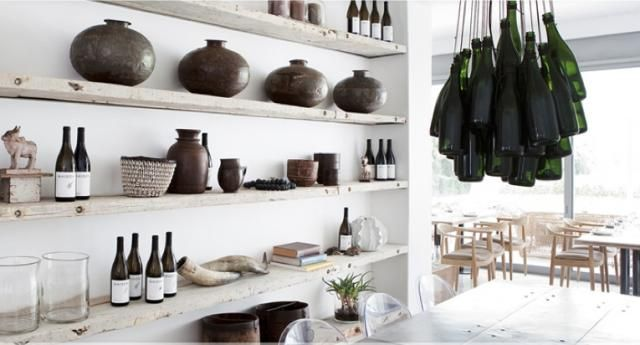 Rough-hewn shelves and  wine bottle chandelier in the tasting rooms at Maison Estate, a South African winery created by designer Chris Weylandt.
