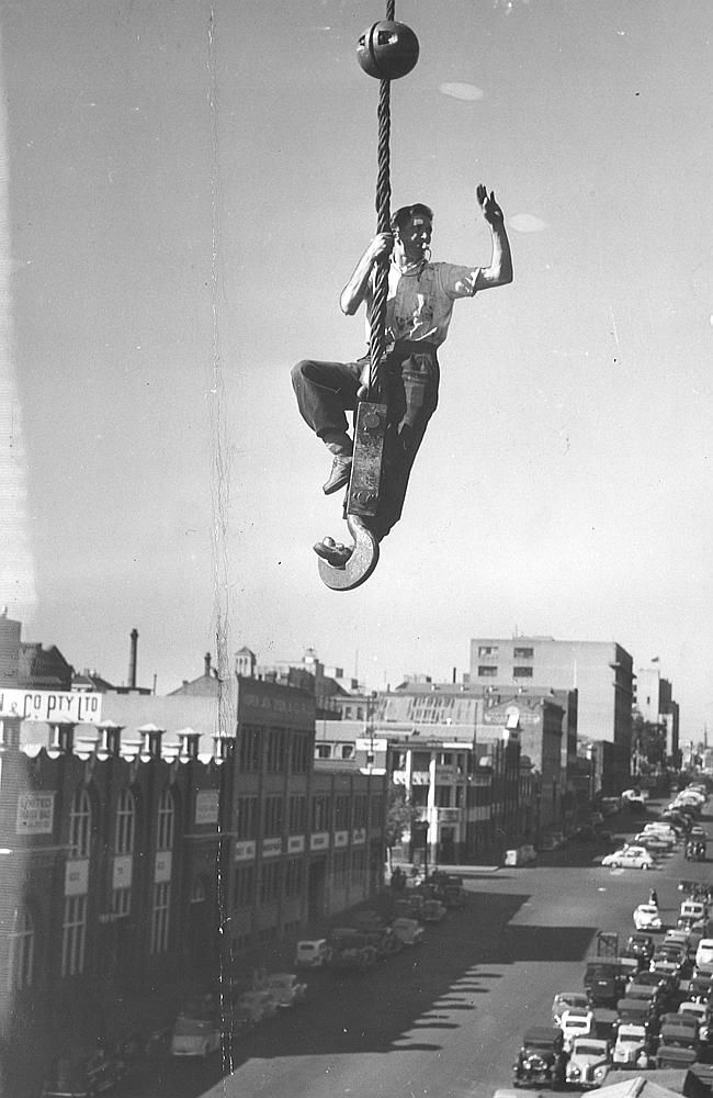 1953: Swinging high above a street, rigger Jack Farley directs his invisible crane driver
