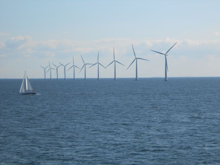10 wind turbines and a sailboat off the coast of Samso, Denmark. An island fueled by green energy.