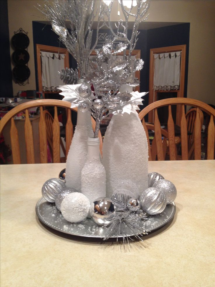 Wine bottles spray painted white, sprayed with adhesive & rolled in Epsom salt for a Christmas centerpiece. Pinterest Success! Perfect for entryway decor too.