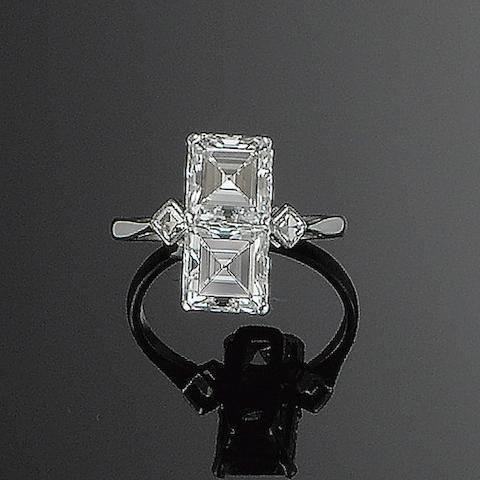 An art deco diamond two-stone ring, circa 1930 The two vertically aligned square step-cut diamonds, each within a four-claw setting, between shoulders of smaller lozenge-shaped stones