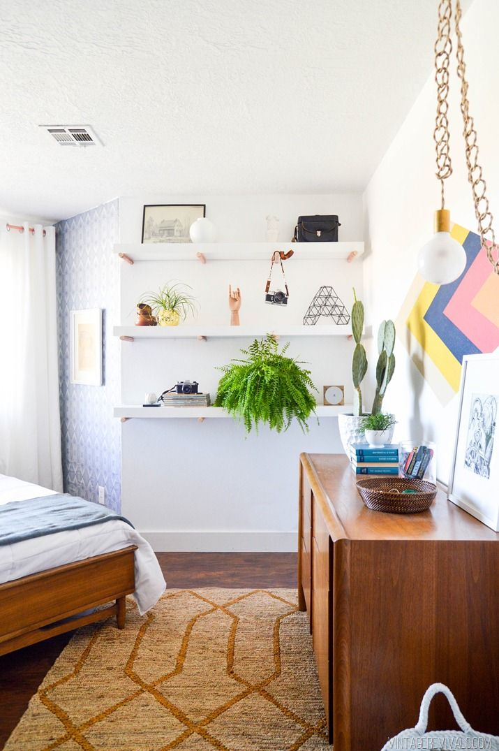 White walls, white shelves, brown cabinet, and printed tan rug