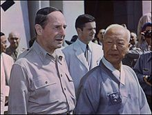 Douglas MacArthur with US puppet, Syngman Rhee. Americans helped him take power. Part of the old, moneyed elite, and so anti-Communist. He was also Christian. Rhee aligned himself with the  collaborators of the Japanese and attacked left-leaning peasant associations that were popping up. Syngman Rhee's authoritarian presidency lasted ten more years until 1960, when following popular protests against a disputed election, he resigned. More than 200,000 perished under his reign of terror.
