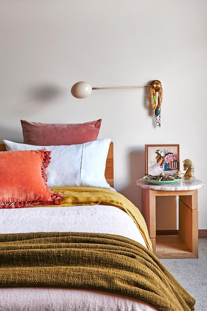 Warming tones of pink, orange and mustard create a cosy feel in this colourful master bedroom. Photo: Nikole Ramsay   Styling: Amber Lenette   Story: real living