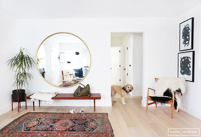Modern and bright entry with Oriental rug, safari style chair, and large round mirror / designed by Amber Lewis of Amber Interiors