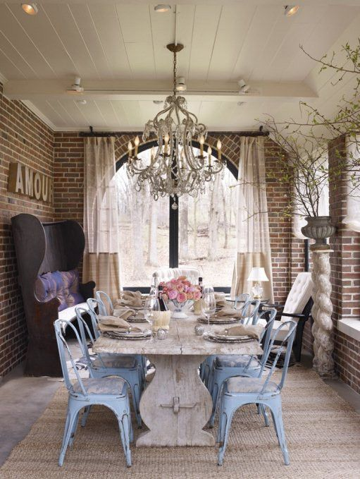 So many wonderful things in one space...vintage blue chairs, brick, ceiling, white trestle table, chandelier, arched window.