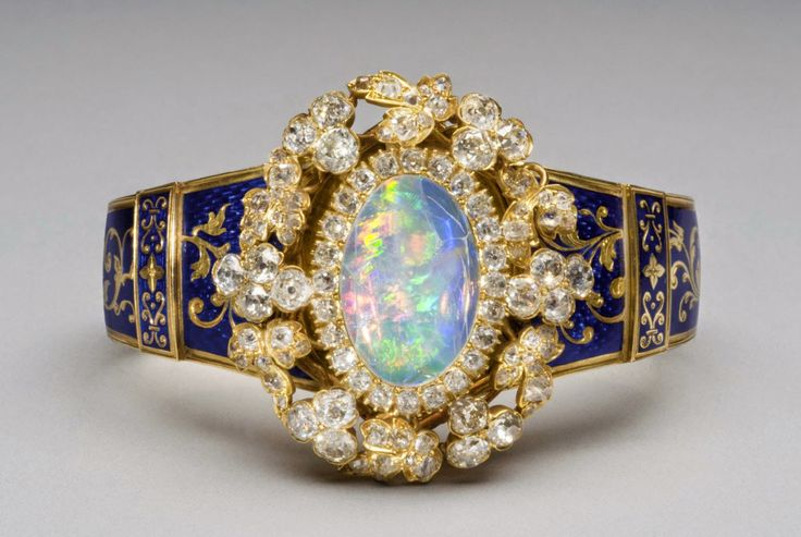 """tiarascrowns: """" Victorian Opal Bracelet A Victorian bracelet, circa 1849 France, featuring a white opal centerpiece surrounded by diamonds, connected to a gold bangle with blue enamel decorations. Inside the bracelet are two inscriptions: """"May 1849″..."""