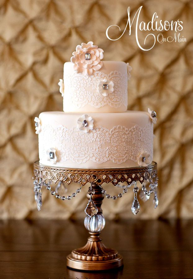 I created this for a recent magazine publication.  The cake is covered in a very pale blush colored fondant.  I then stenciled on the lace pattern.  I hand made little fondant blossoms with rhinestone centers, then made one large deeper blush fondant blossom.  I purchased the stand from Lamps plus.  Photo by Kevin Paul Photography.