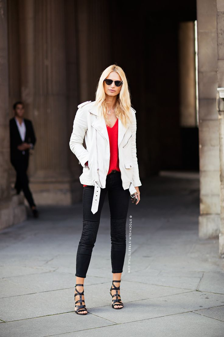 White moto jackets layered over a red top, paired with black cropped pants #StreetStyle // Photo via Stockholm Street Style