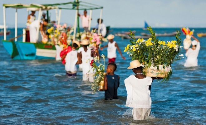 Candomble devotees carry flower baskets onto a boat during the ritual ceremony in honor to Yemanja in Amoreiras, Bahia, Brazil.