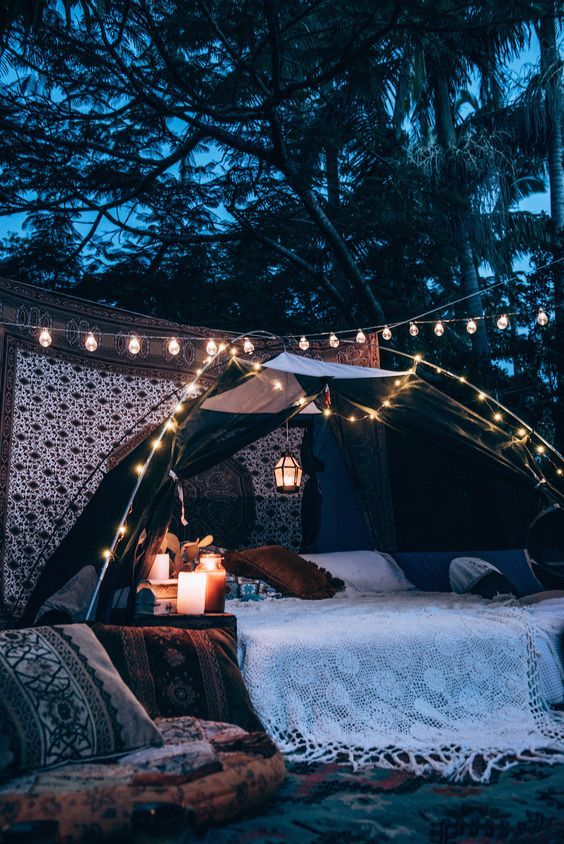The Best Outdoor Lighting and Decor for Summer | outdoor bed under strands of lights from 'Spell Designs'