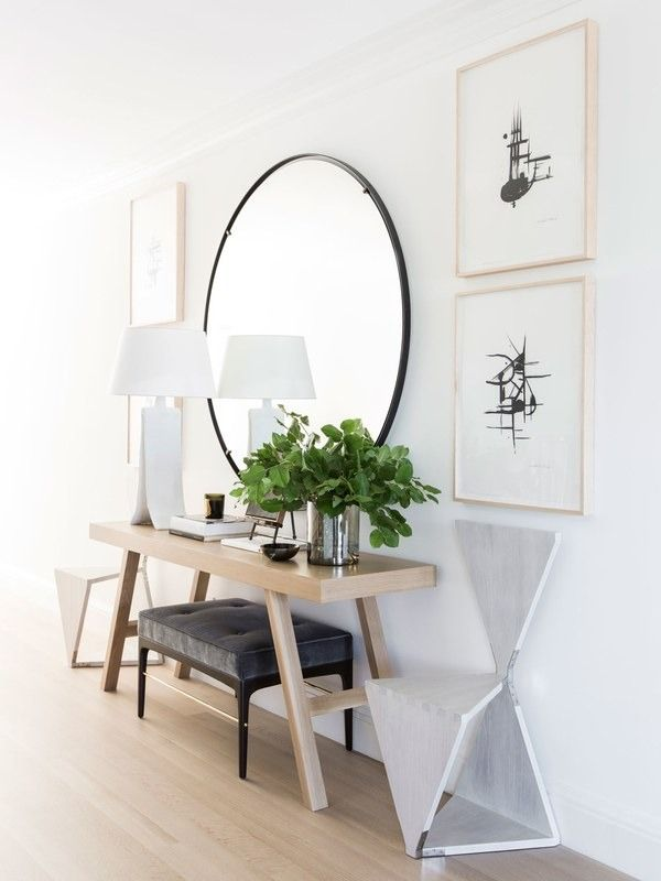 The entryway was left white and welcoming, with hardwood floors that mimic the light wood used in the custom table | archdigest.com
