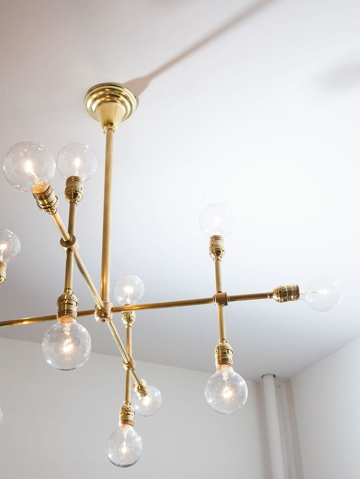 After spotting a similar chandelier at Octavia & Brown's NYC showroom, Dash commissioned designer Paul D. Pisanelli to create this 12-arm brass rendition completed with clear, 25-watt globe bulbs from Home Depot.