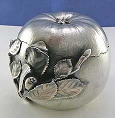 Very unusual Gorham sterling silver apple tea caddy with hinged lid and textured surface. Applied leaf decoration. The lid fits together with the base with a jagged irregular seam as if the apple had been peeled open. Dated 1883 with the Gorham date letter P. The clasp is a bug that rotated to secure a small bar on the top lid.