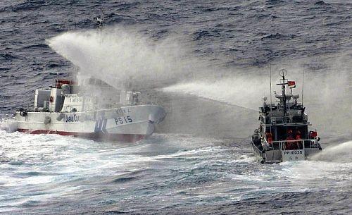 領海内で放水しあう海上保安庁の巡視船(左)と台湾の巡視船(25日午前、読売機から)=清水健司撮影