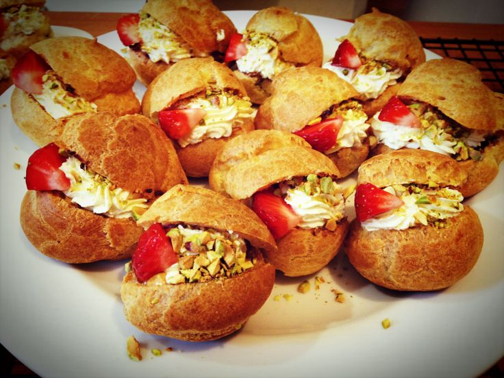 profiteroles stuffed with whipped cream, strawberry and pistachio