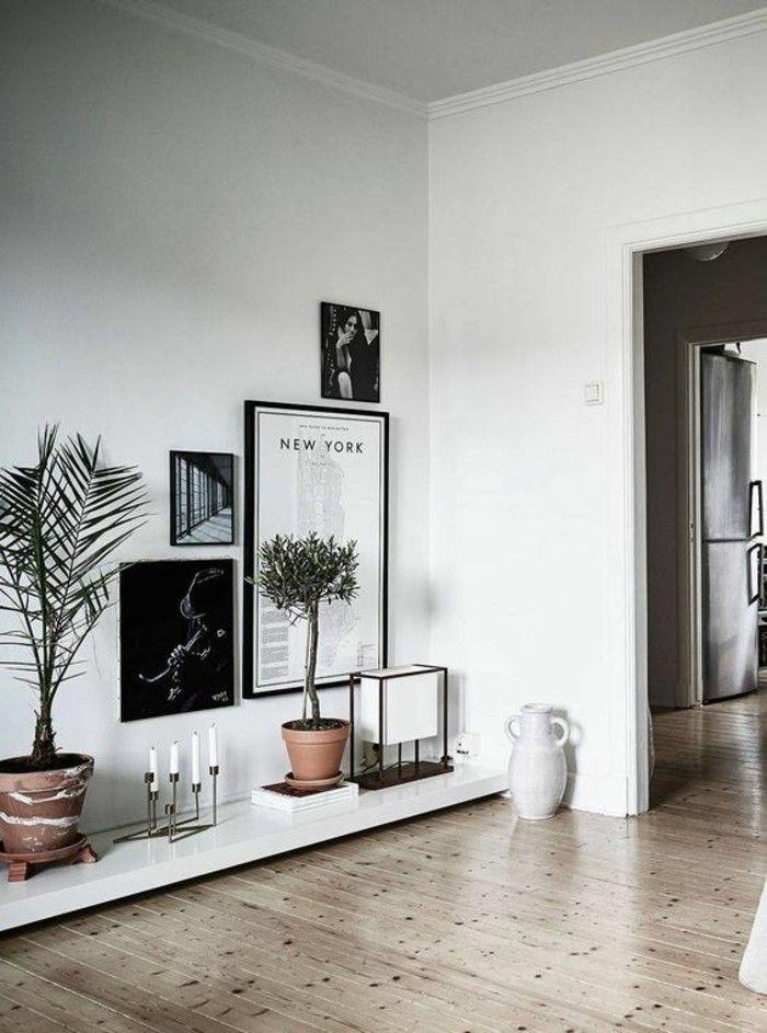 salon chic avec sol en parquet clair, mur blanc tableaux d art muraux, plante verte d'intérieur