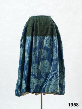 1770 - 1800 Halland, Årstads hd, Eftra Kjol sydd av 7 våder storblommig ylledamast av högsta kvalitet kamgarn med glättad yta, stora gröna blommor på klarblå botten. Bred skoning på insidan runt kjolkanten av oblekt linnelärft. Ylledamast av denna höga kvalitet vävdes främst i Norwich i England. Under slutet av 1700-talet var det högsta mode inom bondeståndet med sådana tyger i framförallt bröllopsdräkterna. Till denna kjol har det gått åt närmare 7 meter av det dyrbara tyget.