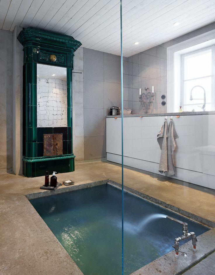 Badrummet är som ett litet spa med nedsänkt badkar. Kakelugnen är som en färgklick där rå betong och vitt kakel för övrigt sätter stilen. Bakom glasväggen som syns som en linje mitt i bild ryms bastun. Foto: Johan Carlson.