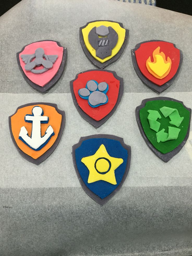 Paw Patrol fondant badges  I made these by printing out a picture of the badges then transferring them on to baking paper making a template for each component of each badge.  I marked out the badges on to fondant and cut fondant out.  I assembled the badges with just a small amount of water between each layer