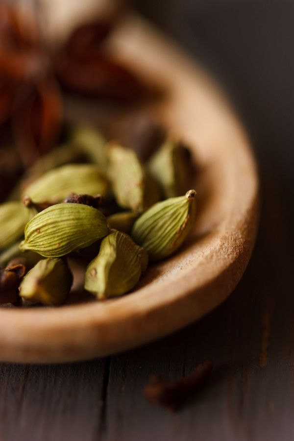 Green aromatic cardamom in a wooden spoon - love cardamom