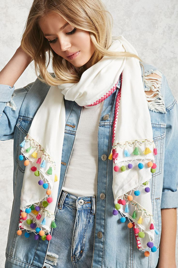 A woven oblong scarf featuring a layered trim with pom poms and tassels and a geo embroidered edge.