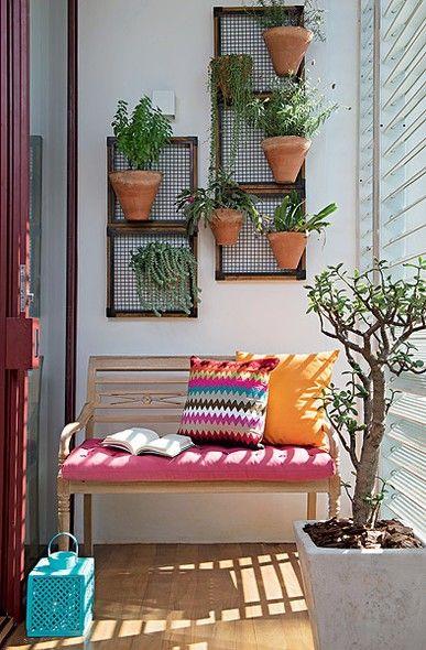 As almofadas coloridas no banco de madeira transformam o ambiente, que ainda encontra espaço para reunir plantas em diferentes tipos de vasos
