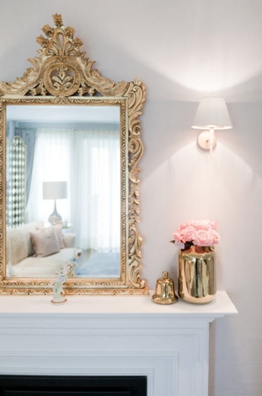 gold mirror and accessories over fireplace