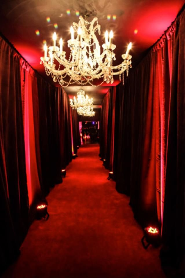 Using pipe-drape and red LED lights and ceiling chandeliers dripping with crystals can create this glorious scene.