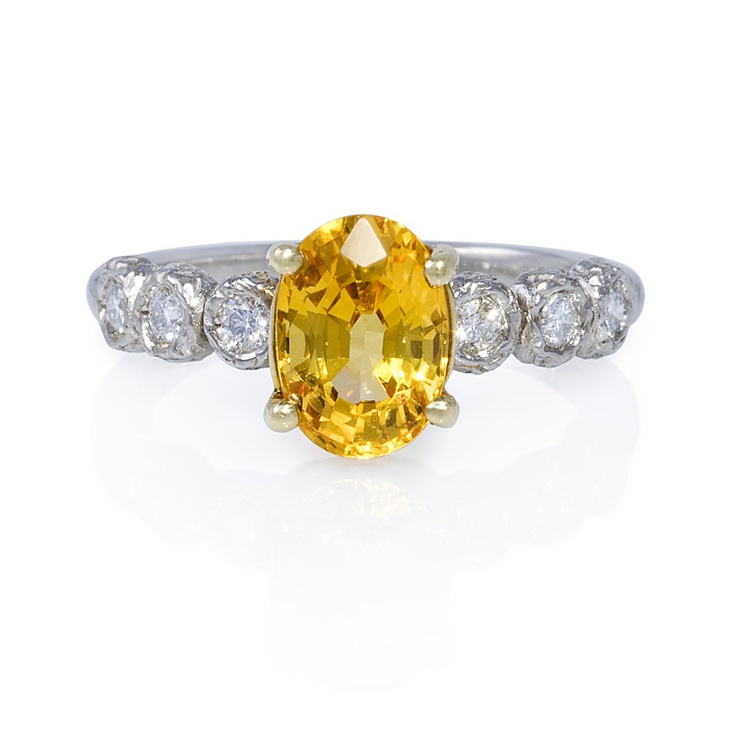 Oval-shaped yellow sapphire engagement ring with diamond-encrusted band.  Similar to Carrie Underwood's canary yellow diamond engagement ring.