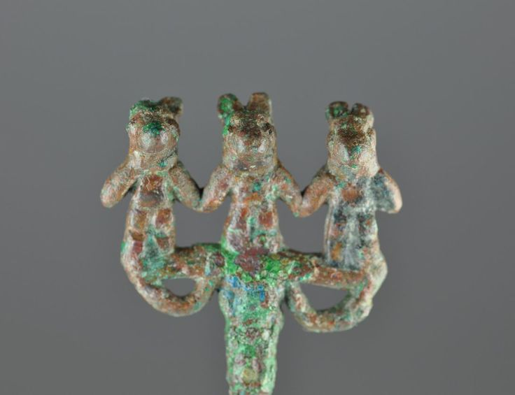 Amlash bronze pin with three animal headed figures holding hands, 1st millenium B.C. Amlash bronze pin with three animal headed figures 10 cm high pin, 2 cm high three figures, unpublished. Private collection