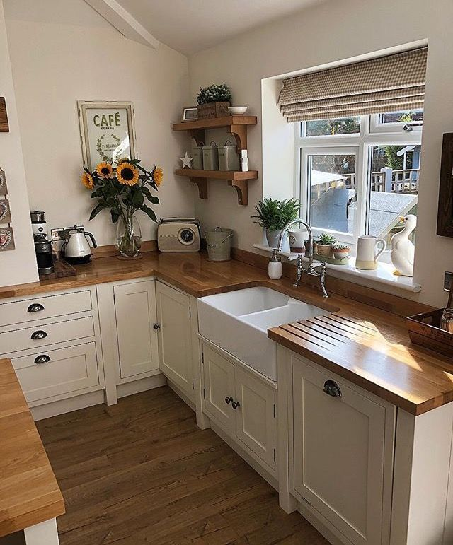 Natural wood worktops with white cabinets and dark drawer handles.