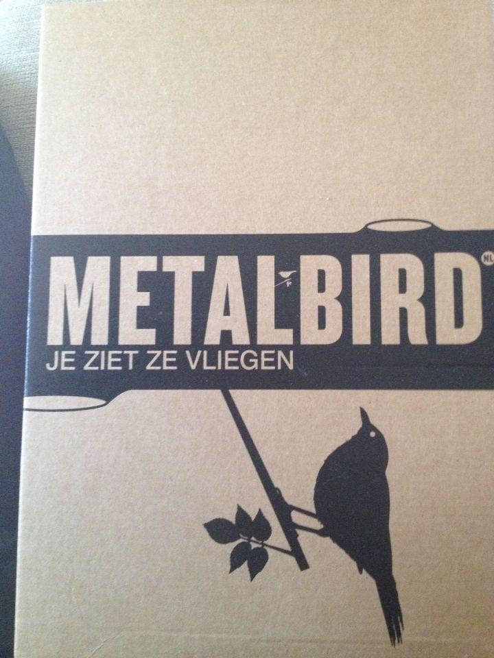 Verpakkingsmateriaal bij een metalen vogel, hoofdletter, bold, breed, horizontaal